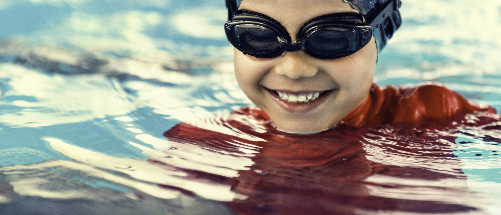 Cool little boy, feeling happy in the pool. Toned image